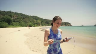 Female jogger walking and listen to the music on the beach, super slow motion 240fps