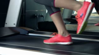 Female legs walking on treadmill machine in gym, super slow motion, 120fps