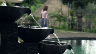 Fountain in swimming pool, walking woman in background, shot at 240fps