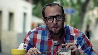 Funny man eating salad and looking to camera in outdoor bar