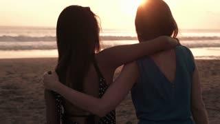girlfriends admiring sunset standing on beach, super slow motion, shot at 240fps