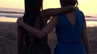 girlfriends admiring sunset standing on beach