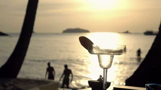 glass of cocktail, people and beach on background, 4k