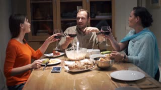 Group of friends drinking red wine by table at home