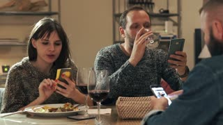 Group of friends looking at smartphones during dinner at home