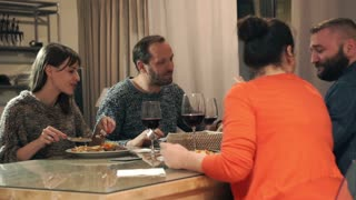 Group of friends talking and looking at something on smartphone during dinner at home