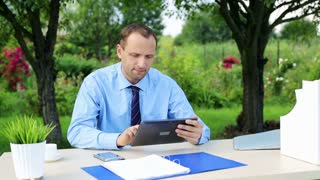 handsome businessman working with tablet in the garden