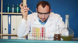 handsome chemist doing science experiment with chemicals