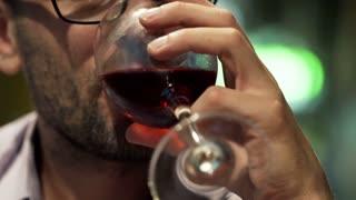 Handsome man drinking wine in bar at night