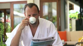 Handsome man in bathrobe reading newspaper by the table at home