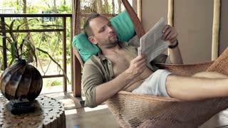 Handsome man read newspaper on hammock on terrace