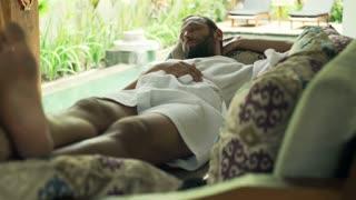 Handsome, young man in bathrobe sleeping on sofa in outdoor villa