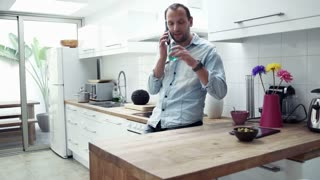 Handsome young man talking on cellphone and drinking water in the kitchen