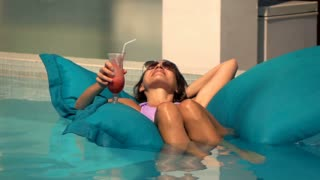 Happy, beautiful woman lying with drink on the mattress in the pool, super slow motion