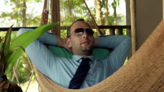 Happy businessman relaxing on hammock, at terrace