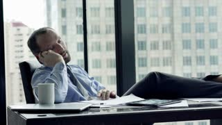 Happy businessman talking on cellphone, sitting by the window in the office
