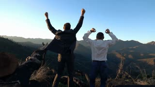 Happy businessmen jumping on the hill, super slow motion