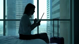 Happy businesswoman reading good news on tablet computer on bed in the hotel room
