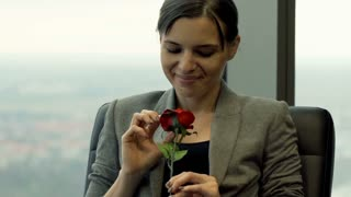 Happy businesswoman smelling rose sitting on armchair by window in the office