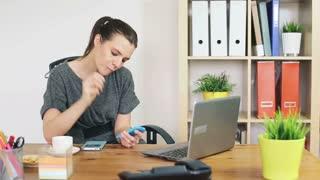 Happy businesswoman texting message on smartphone during work break