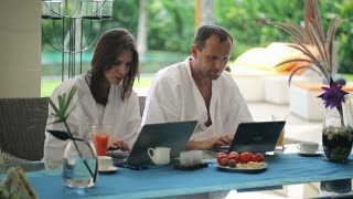 happy couple sitting with modern laptop by the table in luxury villa