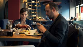 Happy couple taking photos with cellphone of their meal sitting in cafe