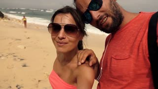 Happy couple taking selfie photo on the beach, super slow motion
