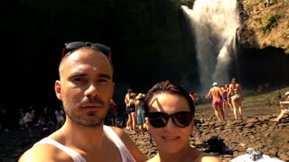 Happy couple taking selfie photo with beautiful waterfall background, super slow motion
