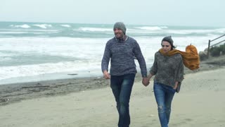 Happy couple walking on the beach on a stormy day