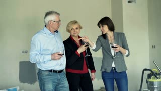 Happy family talking and drinking wine in their new home