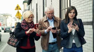 Happy family talking over smartphones walking in city