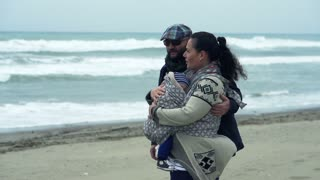Happy family with little child kissing on the beach on a stormy day, 240fps