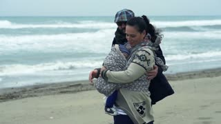 Happy family with little child kissing on the beach on a stormy day,