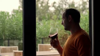 Happy man drinking wine standing by window at home
