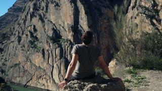 Happy man enjoying mountains sitting on the rocks, 120fps