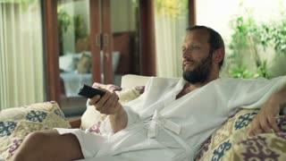 Happy man in bathrobe watching TV on sofa in outdoor villa