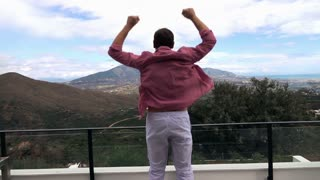 Happy man in pyjama jumping on the terrace with country mountain view, 240fps