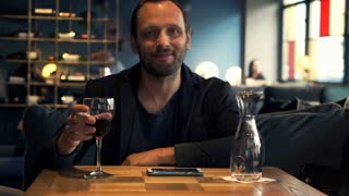 Happy man raising toast to camera and drinking wine in cafe