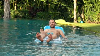 Happy man raising toast with beer lying on the mattress in the pool, super slow motion