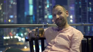 Happy man talking to camera and raising toast to camera with cocktail on terrace with modern city view, 4K