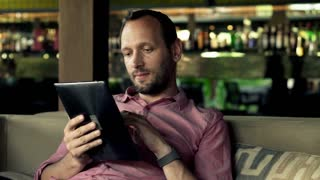 Happy man with tablet computer sitting in bar