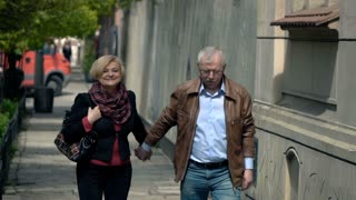 Happy, mature couple walking in city, super slow motion
