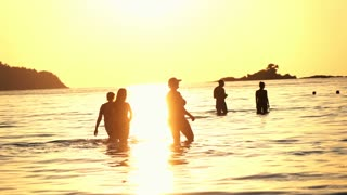 Happy people walking in the sea during sunset, super slow motion