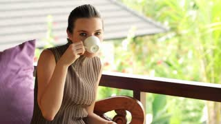 Happy woman drinking coffee on terrace