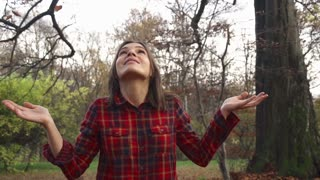 Happy woman enjoying falling leaves in autumn park super slow motion, shot at 240fps