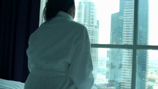 Happy woman in bathrobe stretching arms by window in the hotel room, super slow motion 240fps