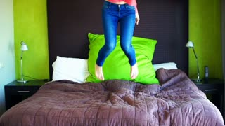 Happy woman jumping on bed, super slow motion, 240fps