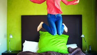 Happy woman jumping on bed, super slow motion