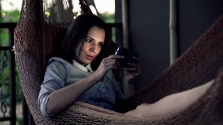 Happy, young businesswoman watching film on smartphone on hammock