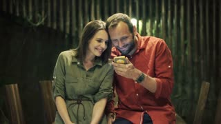 Happy, young couple watching movie on smartphone at home at night